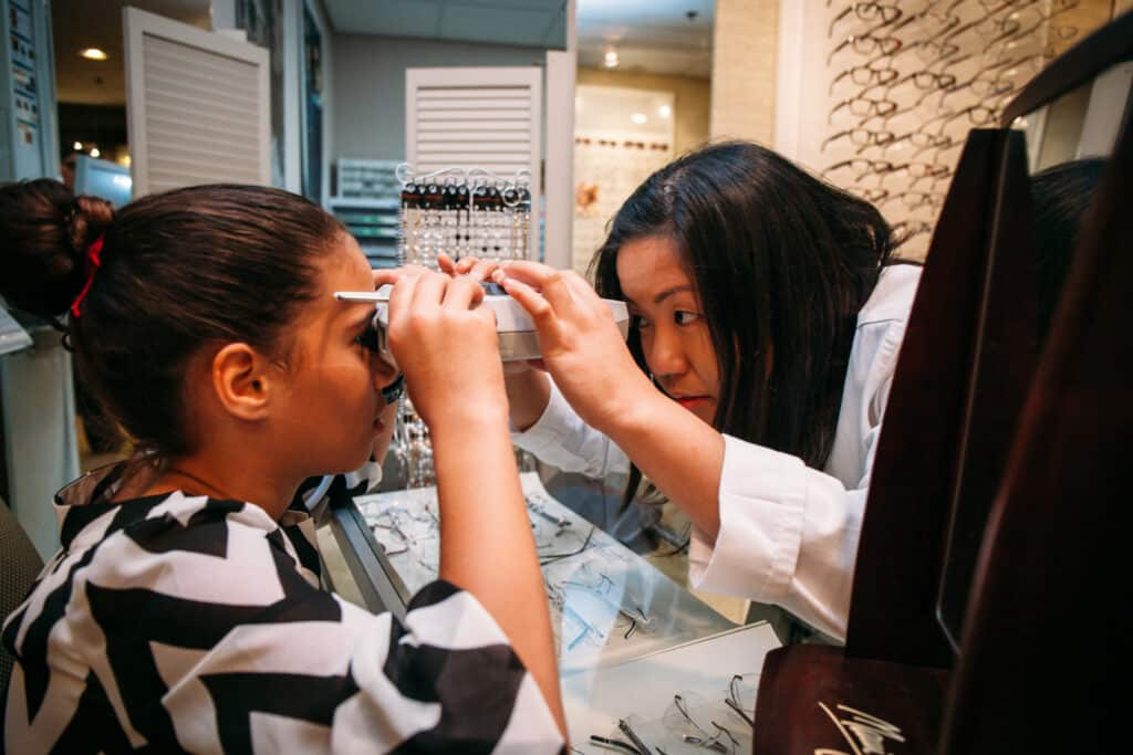 Kristel, our optician, performing measurements on a young patient.