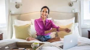 Dr. Rupa Wong at home on her bed with laptop open